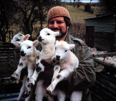 Patrick Tilley, a man of many talents: illustrator, graphic designer, writer and … passionate farmer. Here photographed holding spring lamb in 1983, the same year he wrote Cloud Warrior, the first part of The Amtrak Wars Saga.